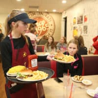 Gold Star franchise waitress serves food to customers